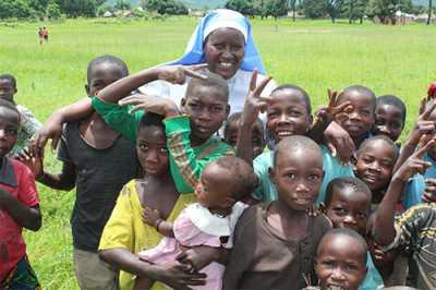 Sr. Maria Telesphora (COLU), ASEC Coordinator – Tanzania poses with children in Sumbawanga.