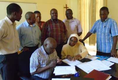 Prof. John Ssbuwufu, Principal Kisbubi Brothers University College signs the MOU. Looking on is Sr. Margaret Kubanze, LSOSF, AU, Secretary General, Uganda.